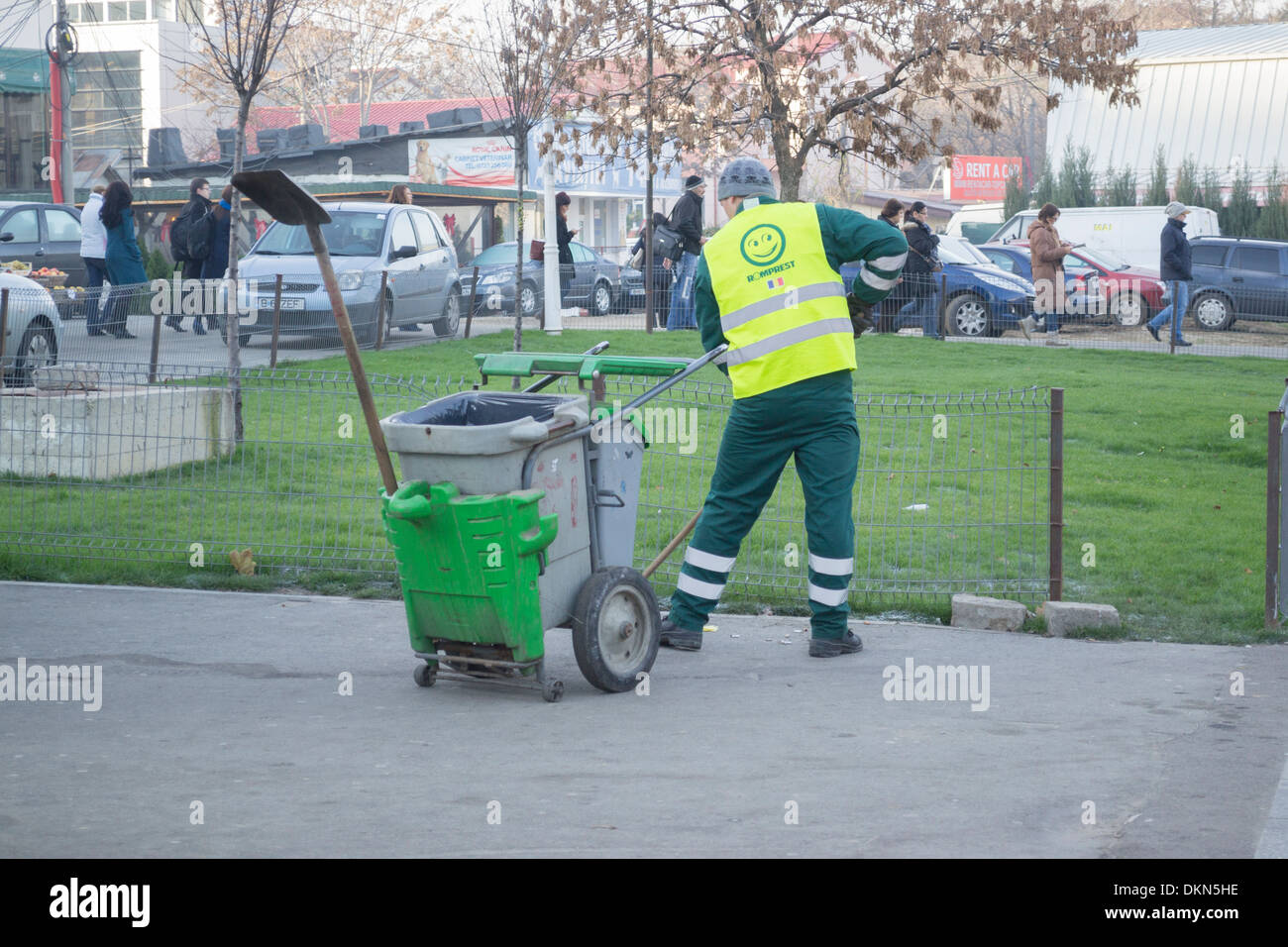 Garbage man cleaning up in front of Aurel Vlaicu subway station, in Bucharest, Romania - Stock Image