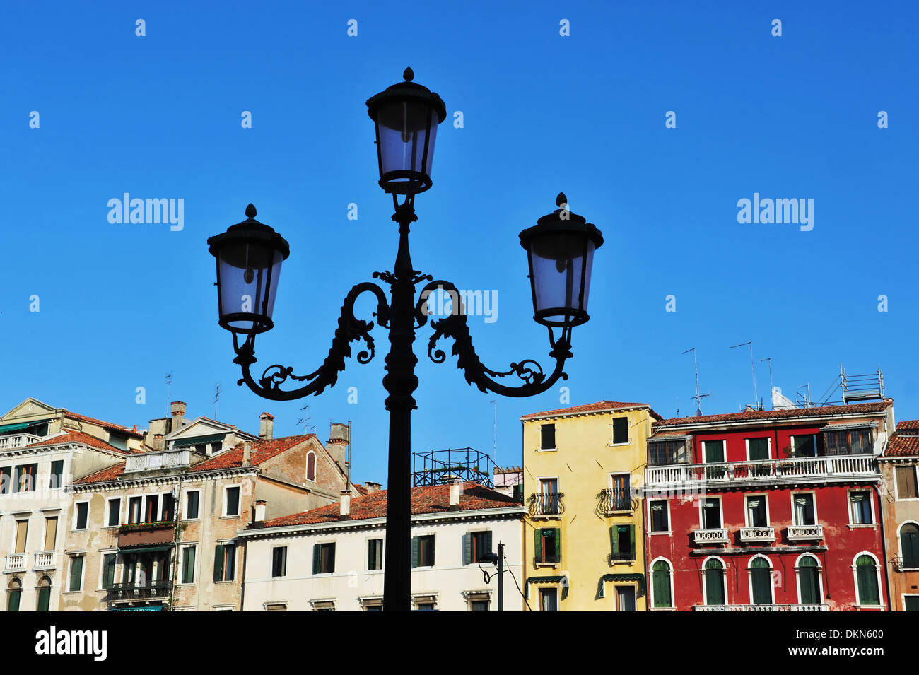 Silhouette of classic old street lamp against a raw of colorful Venetian buildings in Venice Italy - Stock Image