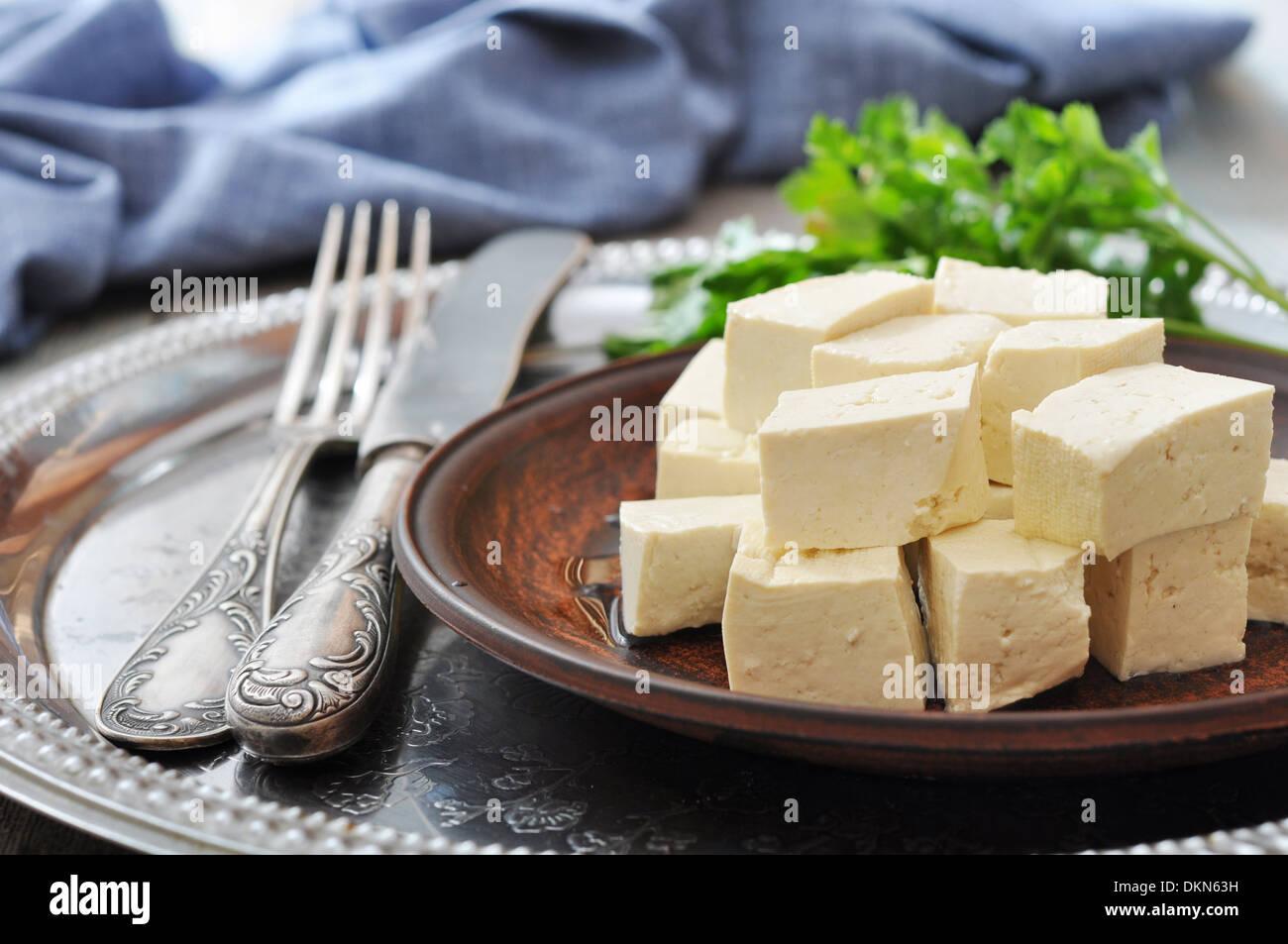 Tofu on plate with fresh tomatos on metal tray - Stock Image