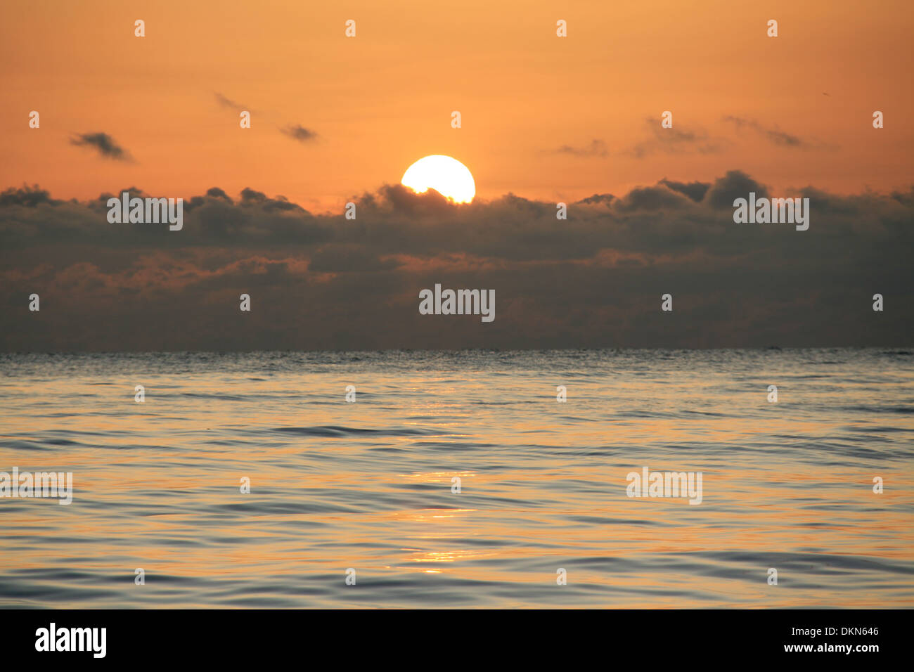 sun rises in cloudy horizon at Caspian sea,Iran;and golden reflection,in early morning is nice.another day is beginning.Soothing - Stock Image