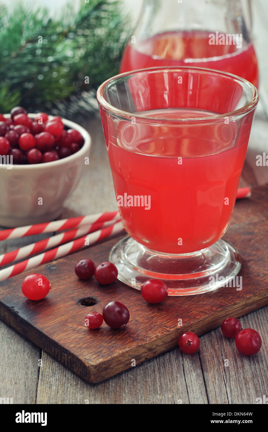 Cranberry juice in glass with fresh berry on wooden background - Stock Image