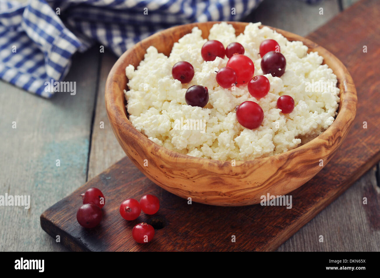 Cottage cheese with fresh cranberry in wooden bowl closeup - Stock Image