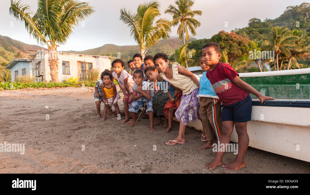 Children sitting on a fibreglass (longboat) on the beach by their village of Tovu at sunset. Tropical island of Totoya, southern Lau Islands, Fiji. - Stock Image