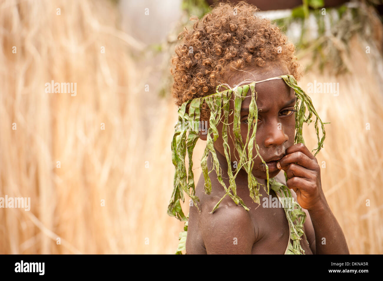 Child amongst performers from Tanna taking part in Fest' Sawagoro, a celebration of kastom, traditional culture in Vanuatu. - Stock Image