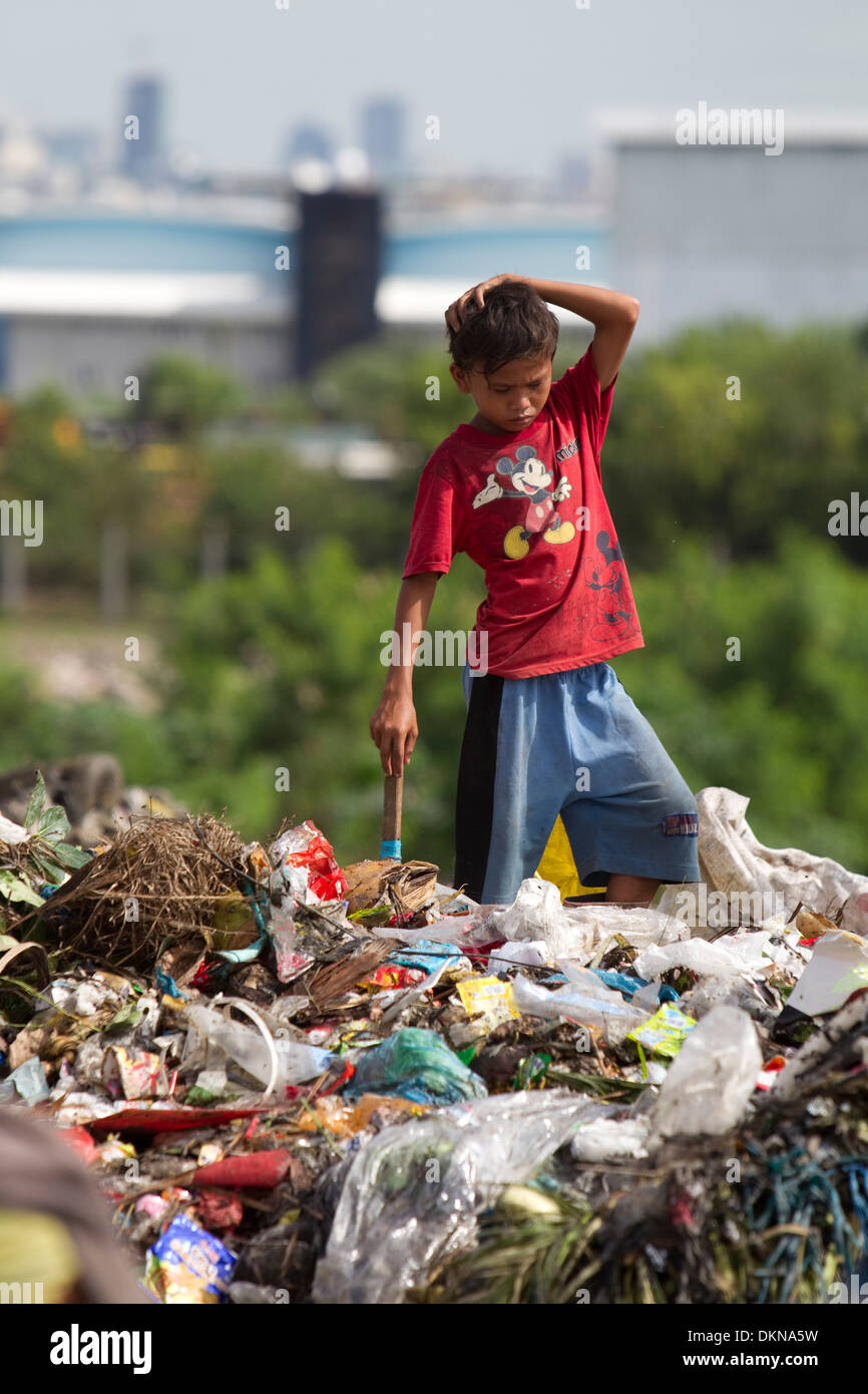 A child scavenging for anything of value within the Inayawan Landfill waste site,Cebu City,Philippines - Stock Image