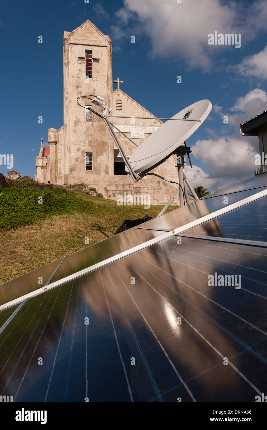 Old and new, solar powered village radio phone in front of the large  Methodist/Wesleyan Church in the village of Stock Photo
