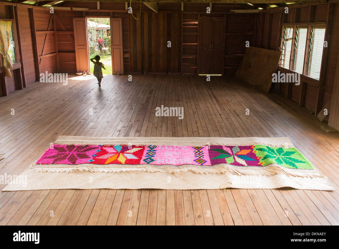 A pandanus and wool mat woven by women as a wedding present on the floor of the community hall, Lomati village, tropical island of Matuku,  Fiji. - Stock Image
