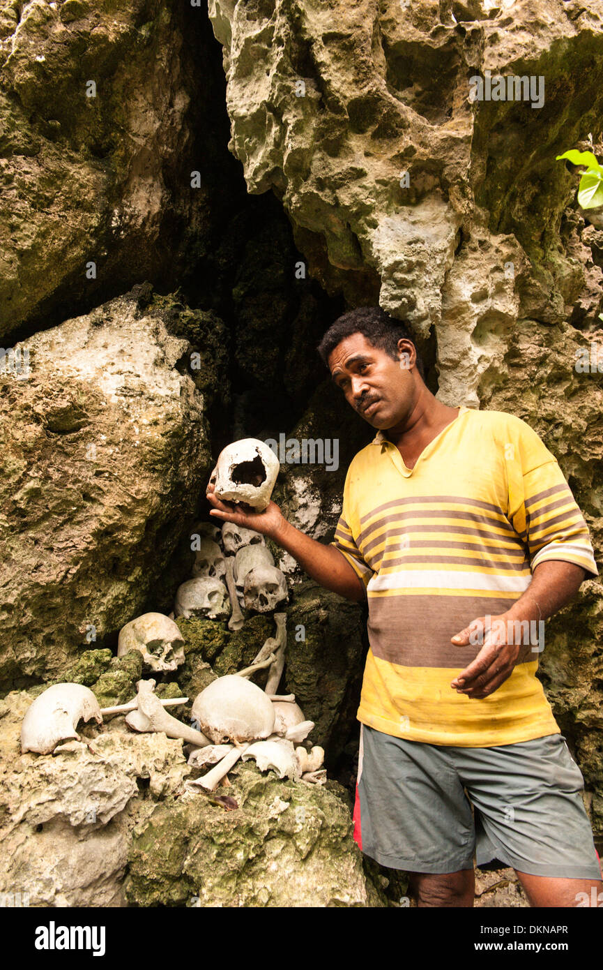 Man holding skull amongst human remains he said were from enemies killed and eaten by his ancestors, renowned warriors. Fiji - Stock Image