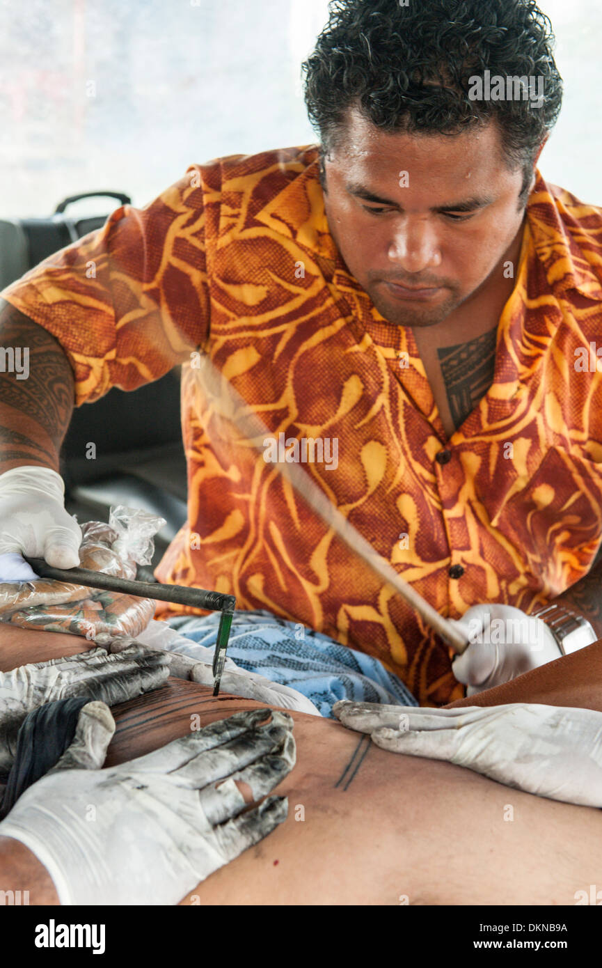 Peter Suluape, a Samoan tatau artist, tattooing a man in a fale near the Government Building in Apia, Samoa - Stock Image