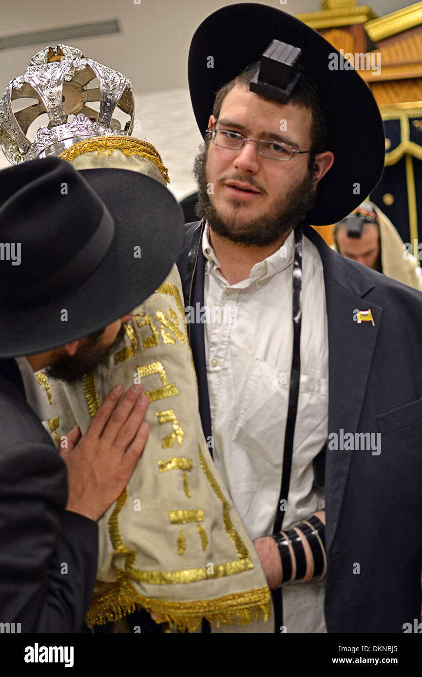 The Torah is kissed by religious Jewish worshipers at morning services at Lubavitch headquarters in Brooklyn, New York - Stock Image