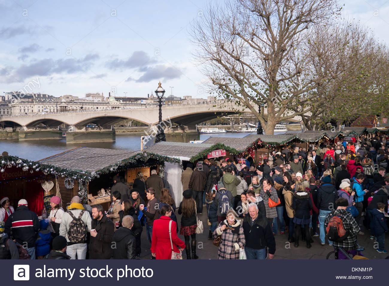 People enjoying the Christmas Market stalls on the South Bank: London. - Stock Image