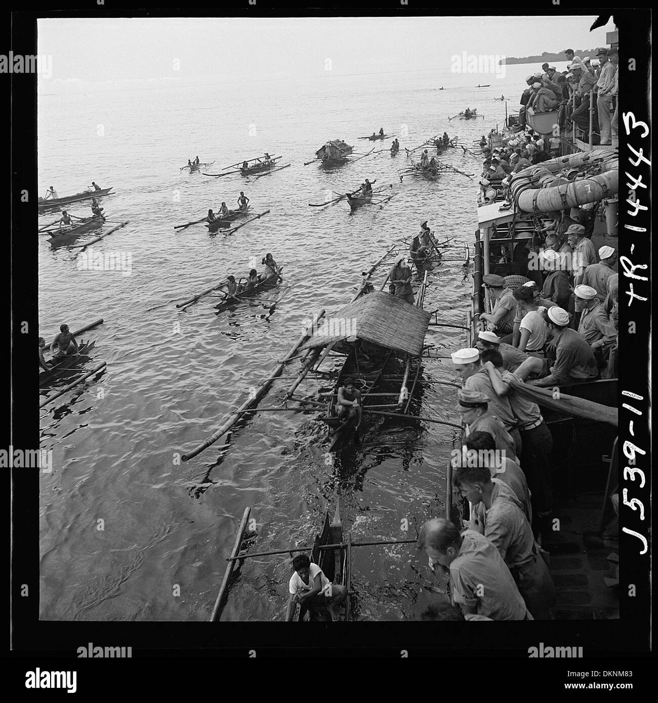 Filipinos with their 'bancas' loaded with wares, paddle out to anchored destroyer to trade with crew. 520952 - Stock Image