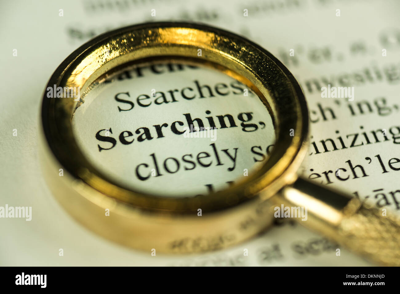 Searching Concept - Macro Image Of A Magnifying Glass Over The Word Searching In A Dictionary - Stock Image