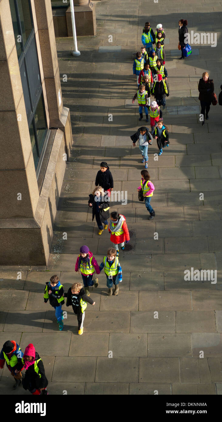A group of young schoolchildren on a field trip viewed from above, walking along the bank of the Thames in London KATHY DEWITT - Stock Image