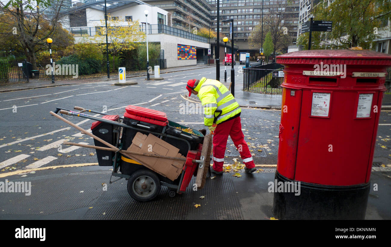 Low paid council worker street cleaner with a broom and dustcart working next to a red postal box in Golden Lane London EC2Y England UK KATHY DEWITT - Stock Image