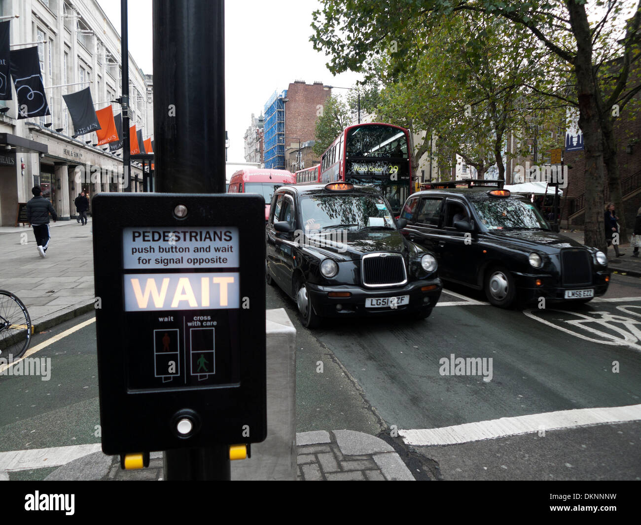 WAIT traffic light sign at pedestrian crossing with black taxi cabs waiting in Tottenham Court Rd London UK KATHY DEWITT - Stock Image