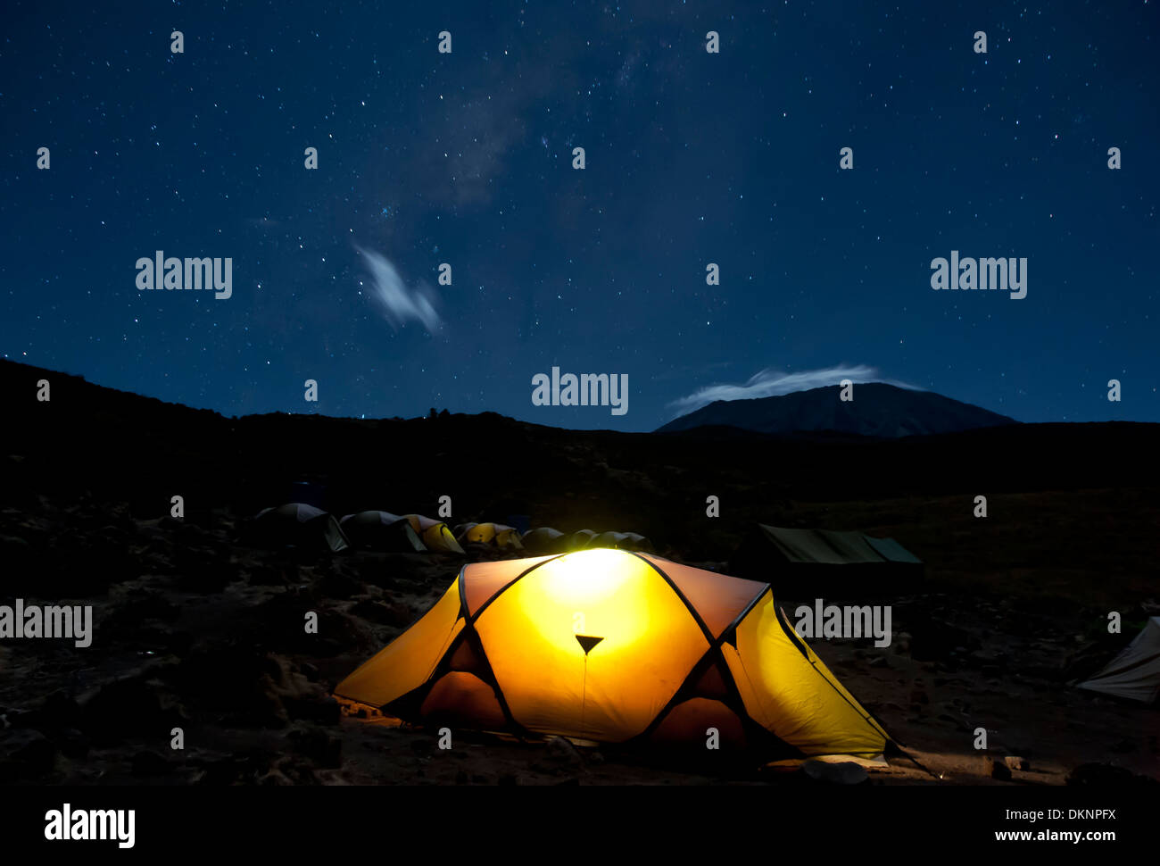 Kikelelwa Cave campsite on Rongai Route at night with Kilimanjaro shrouded in clouds under the stars and milky way - Stock Image