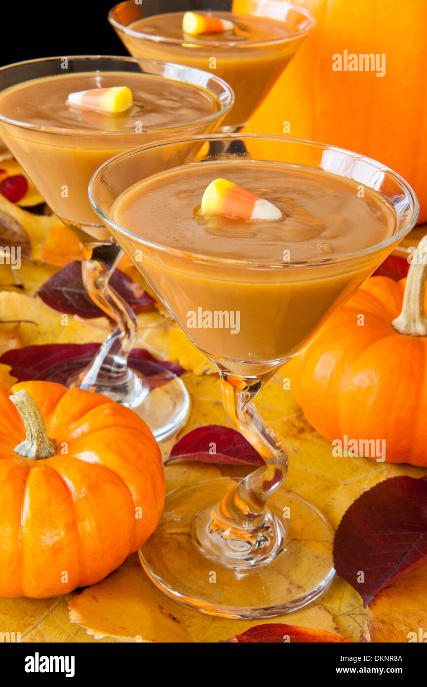 Martini glasses filled with butterscotch pudding decorated with candy corn accompanied by colorful fall leaves and pumpkins - Stock Image