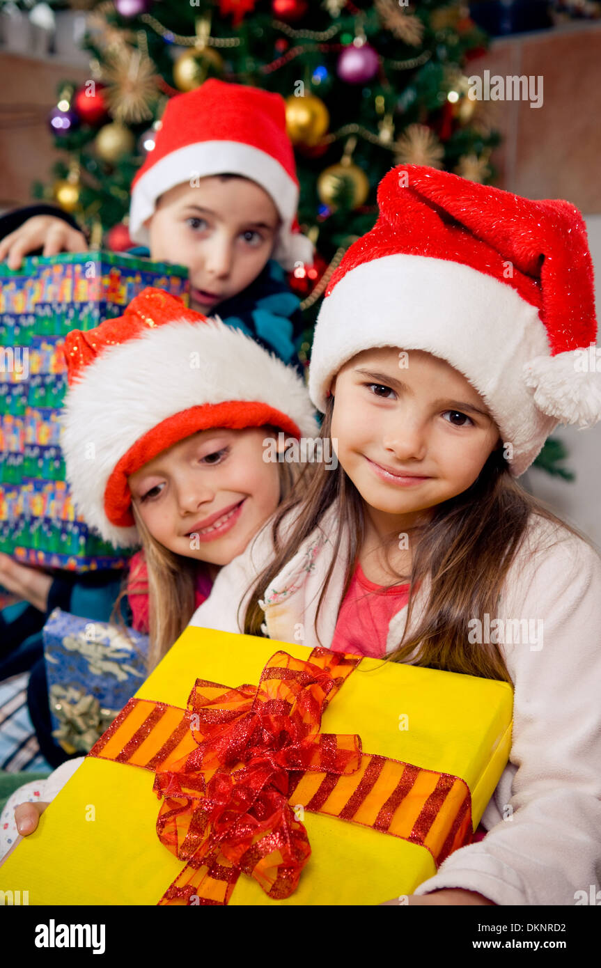 Christmas morning. Happy kids in pajamas holding their christmas gifts. - Stock Image