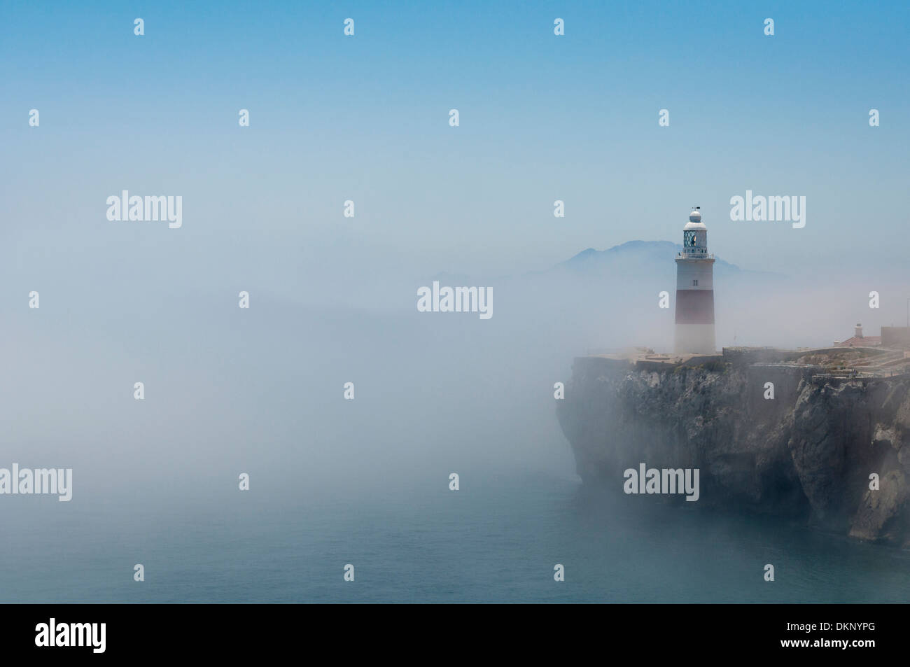 Gibraltars lighthouse at Europa Point standing in the mist with Africa in the distance. - Stock Image