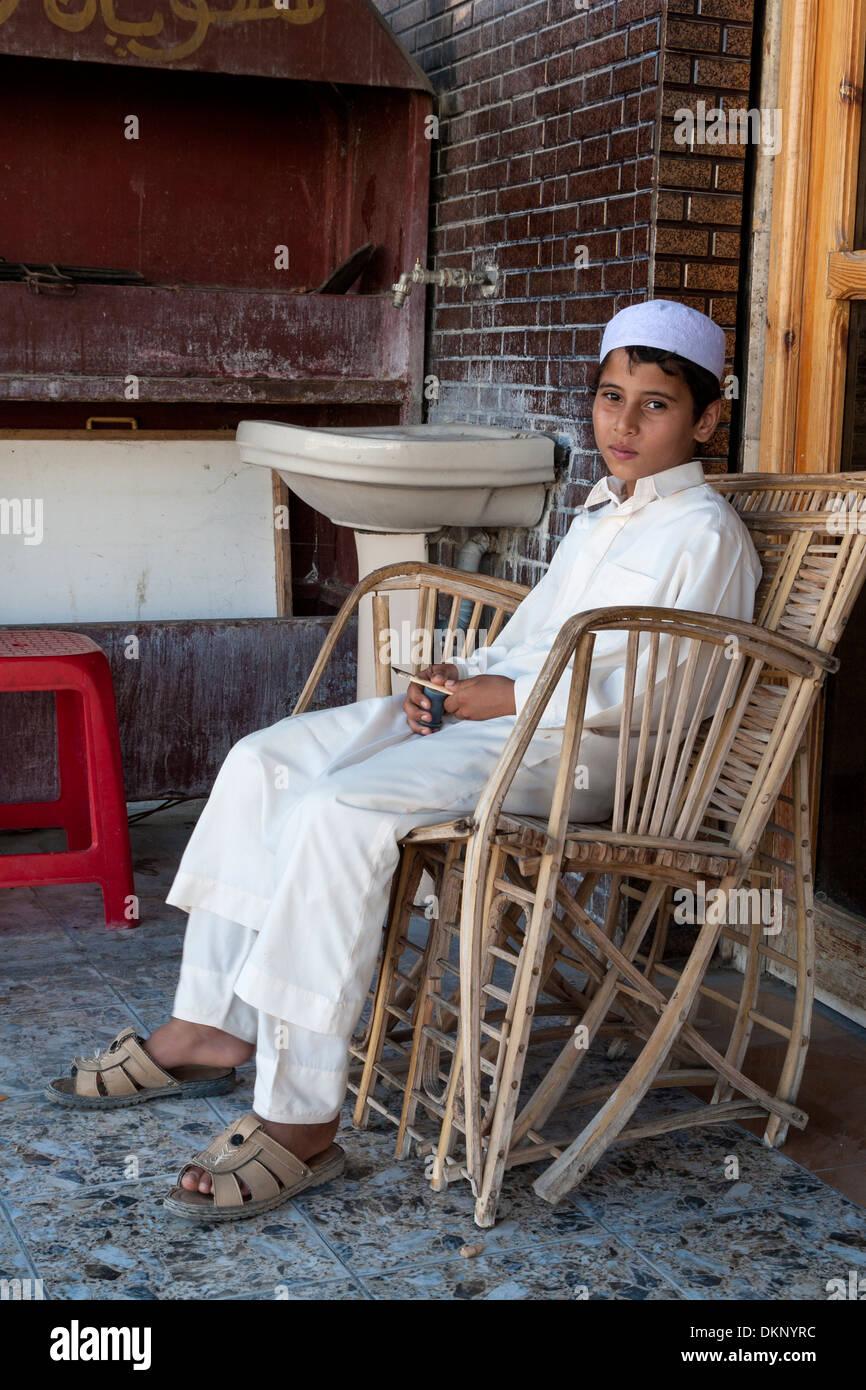 Libya, Zliten. Libyan Boy in Traditional Hat and Juba, a lightweight, white overgarment. - Stock Image
