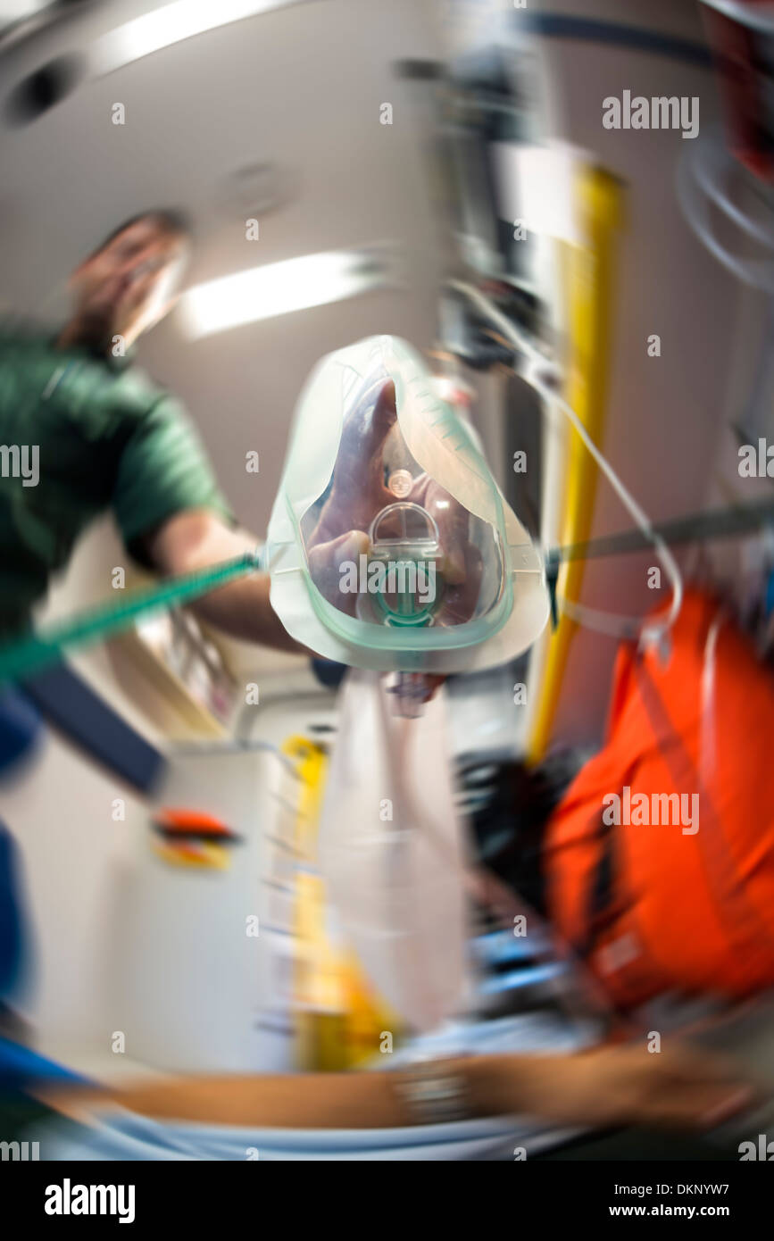 Looking through the eyes of the patient and seeing an Ambulance man putting an Oxygen mask on. - Stock Image
