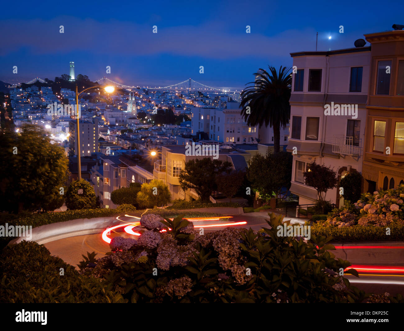 A night view looking down Lombard Street in San Francisco.  Coit Tower and the Bay Bridge are in the distance. - Stock Image