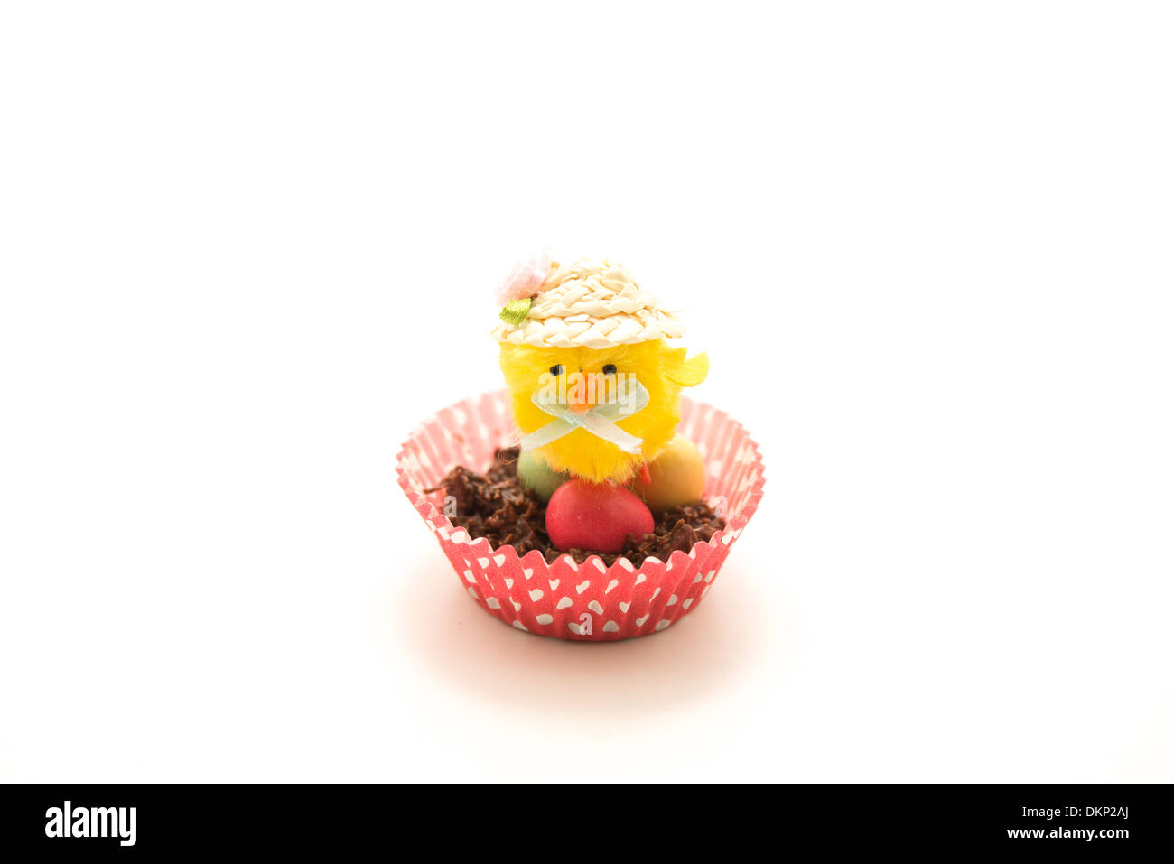 Little Yellow Easter Chick Toy sitting on a Chocolate Egg nest - Stock Image
