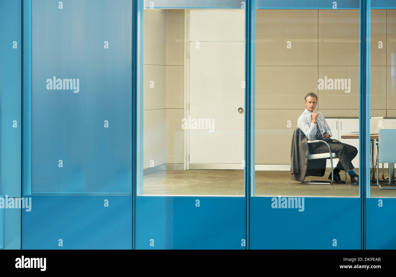Businessman sitting in conference room Stock Photo