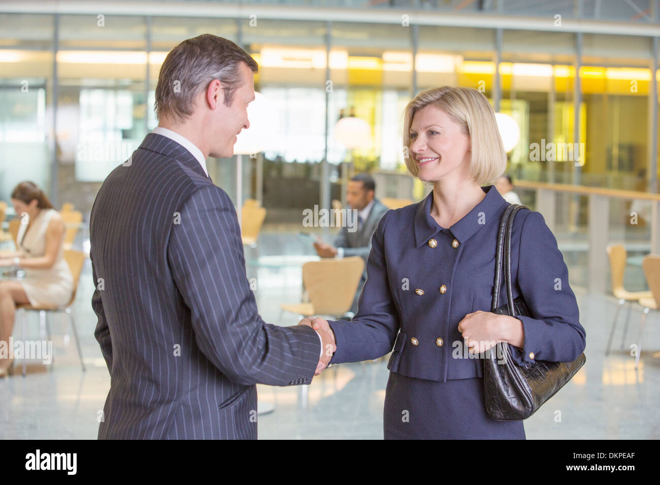 Business people shaking hands in office - Stock Image
