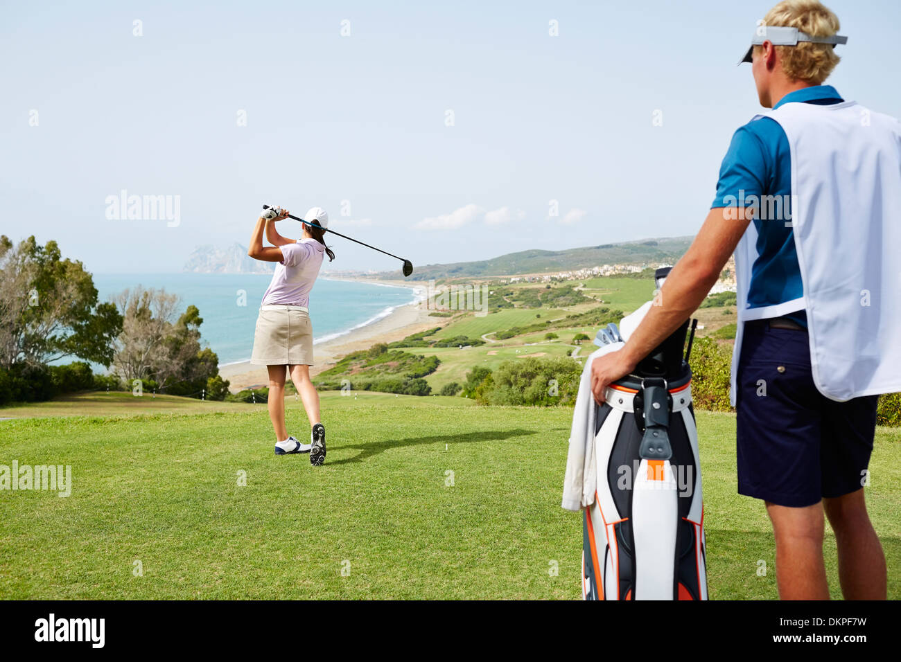 Caddy watching woman tee off on golf course overlooking ocean - Stock Image