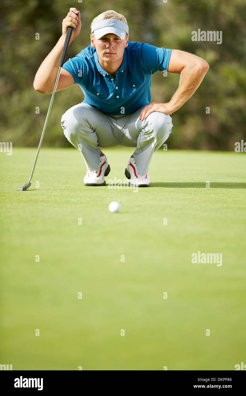 Man preparing to putt on golf course - Stock Image