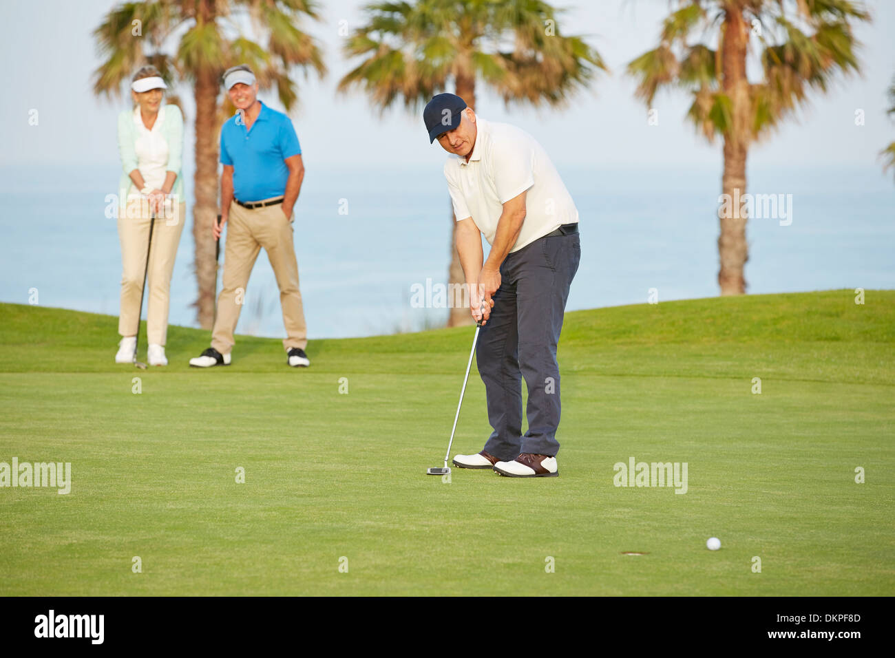 Senior friends playing golf on course - Stock Image