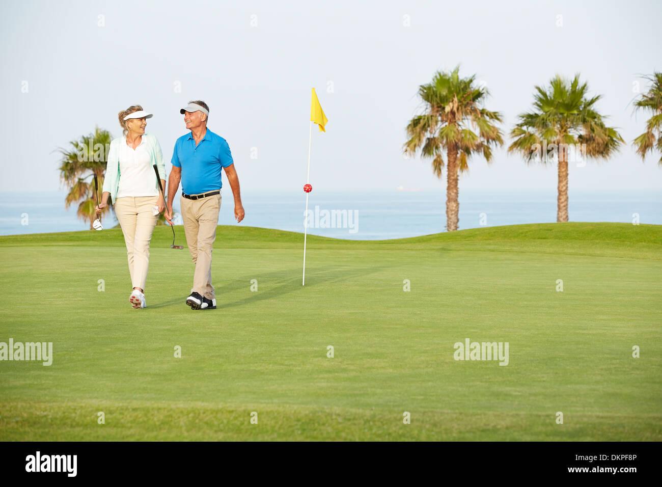 Senior couple walking on golf course - Stock Image
