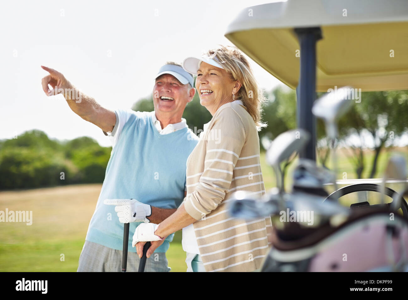 Senior couple standing next to golf cart - Stock Image