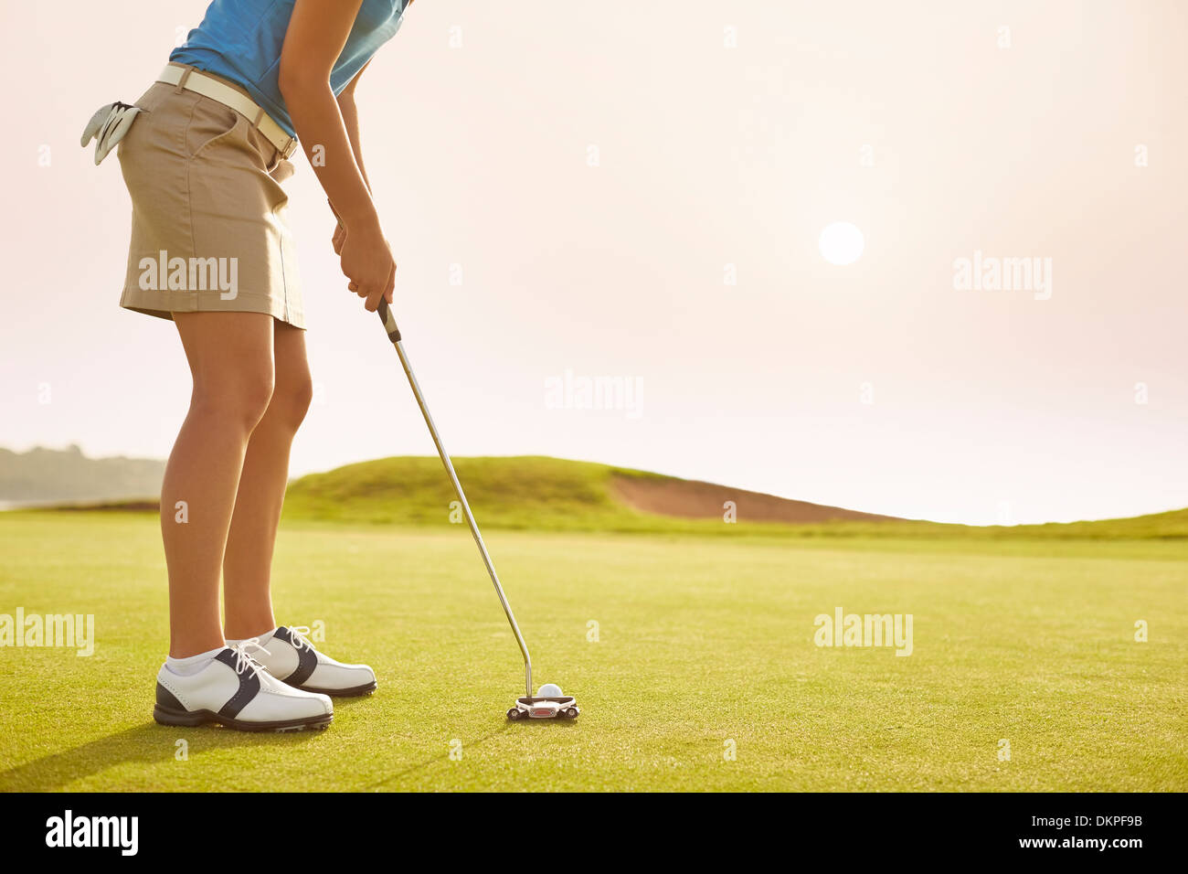 Woman putting on golf course - Stock Image