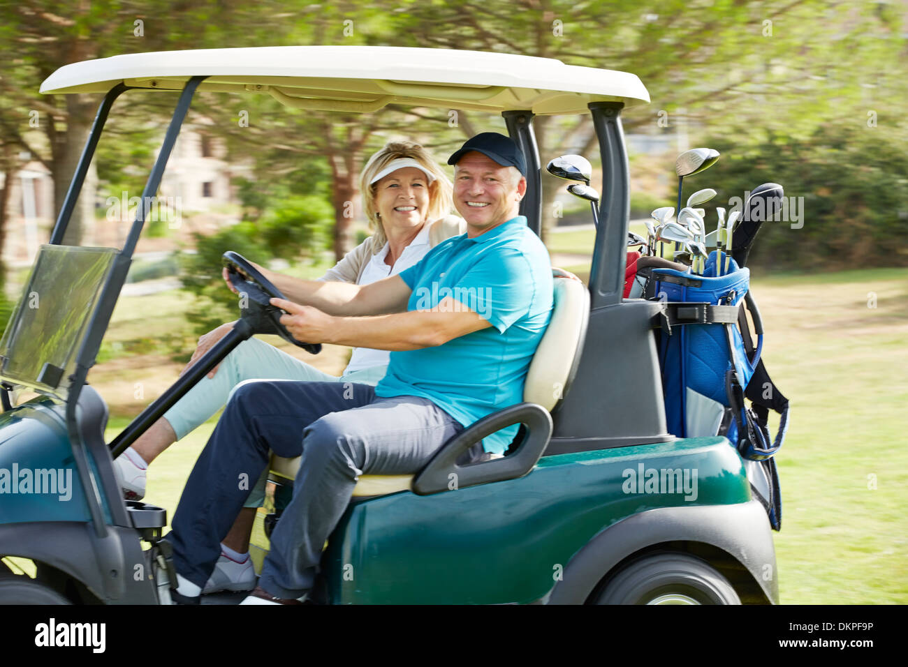 Senior couple driving golf cart on course - Stock Image