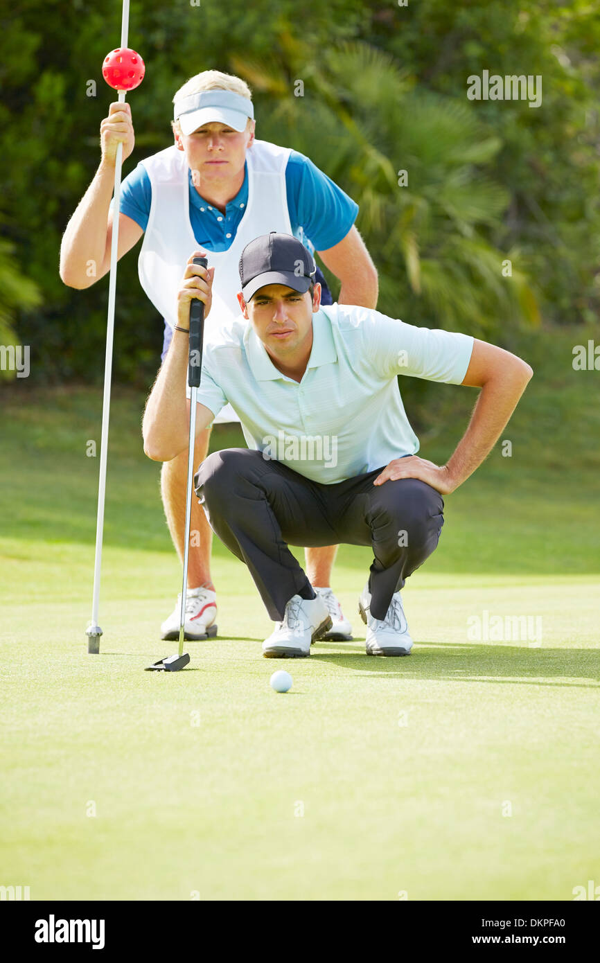Caddy and golfer on putting green - Stock Image