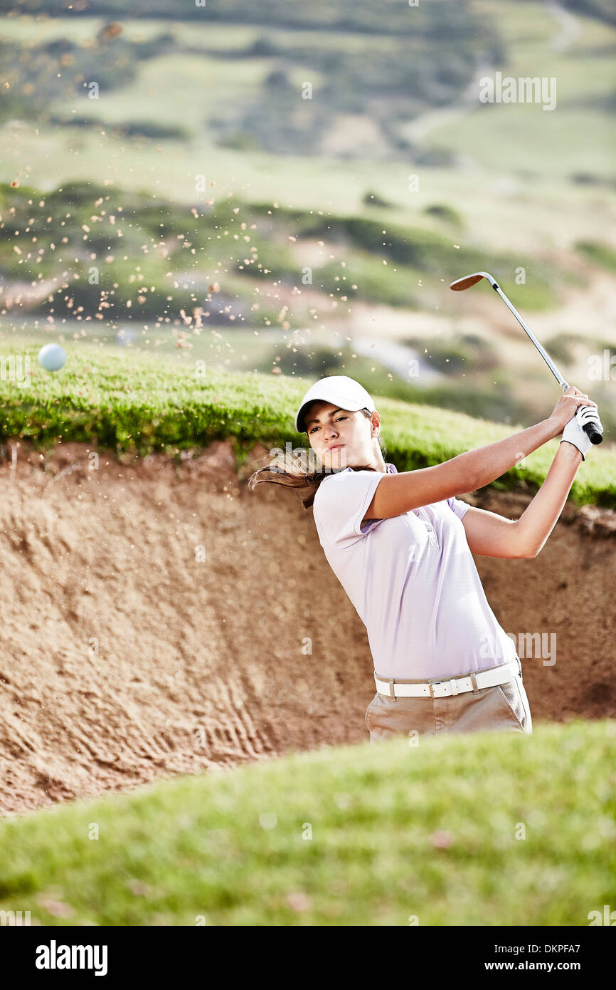 Woman swinging from sand trap on golf course - Stock Image
