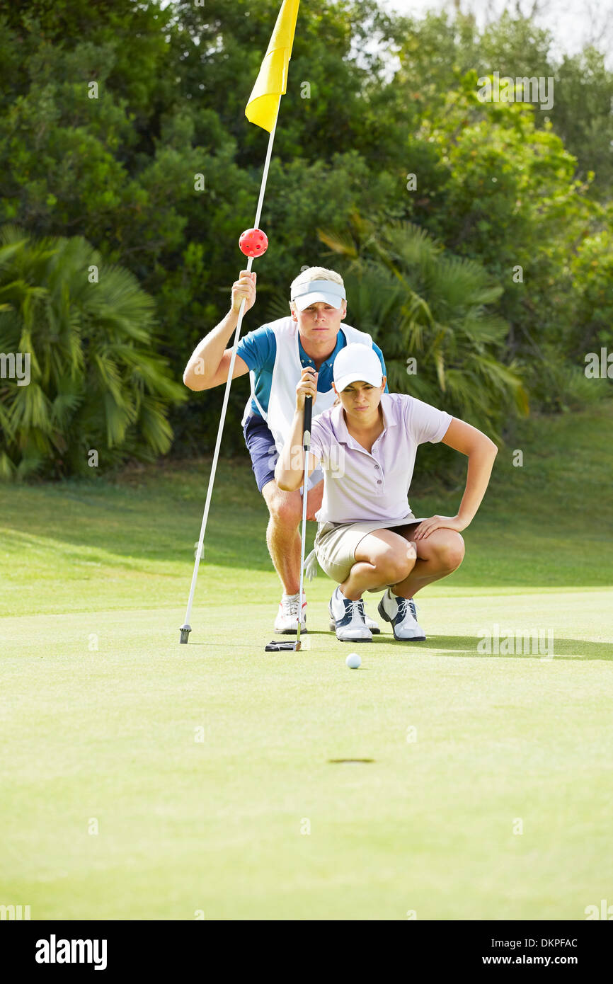Caddy and golfer preparing to putt - Stock Image