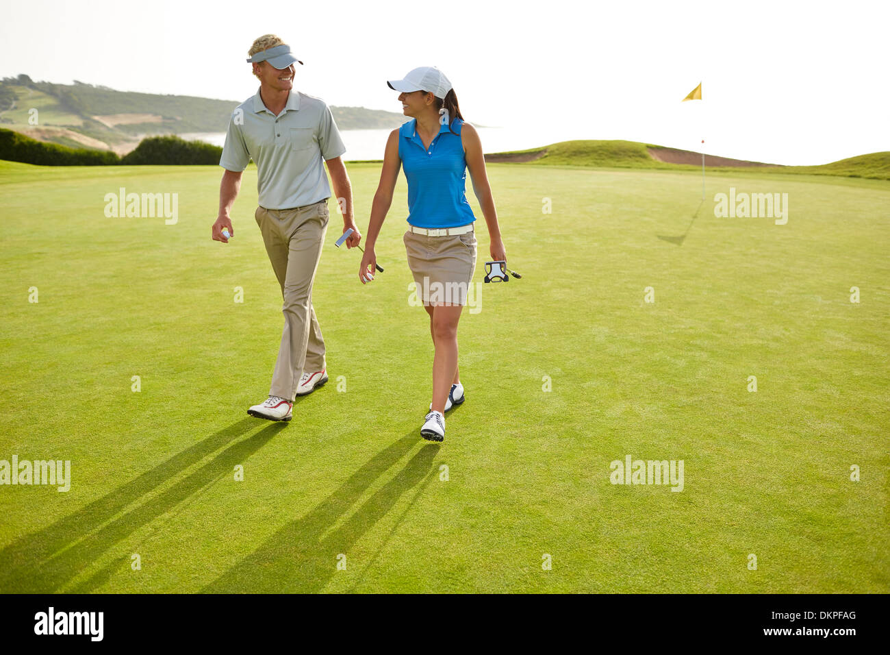 Couple walking on golf course - Stock Image
