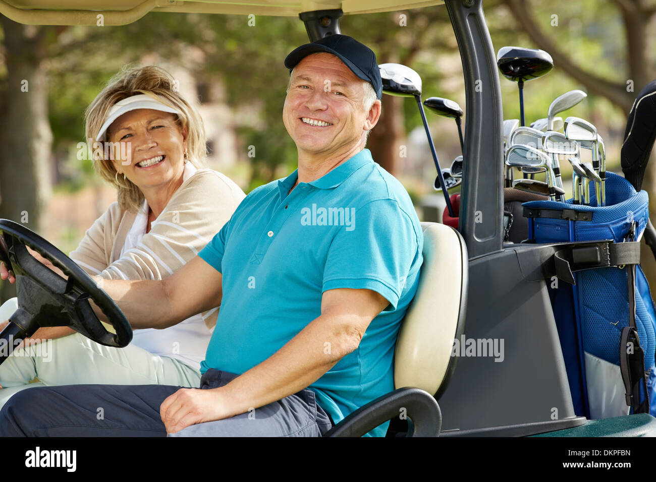 Senior couple smiling in golf cart - Stock Image