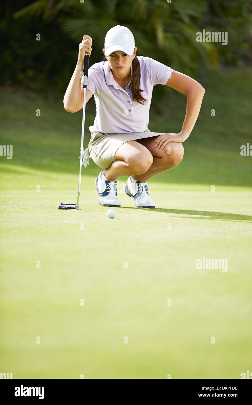 Woman preparing to putt on golf course - Stock Image