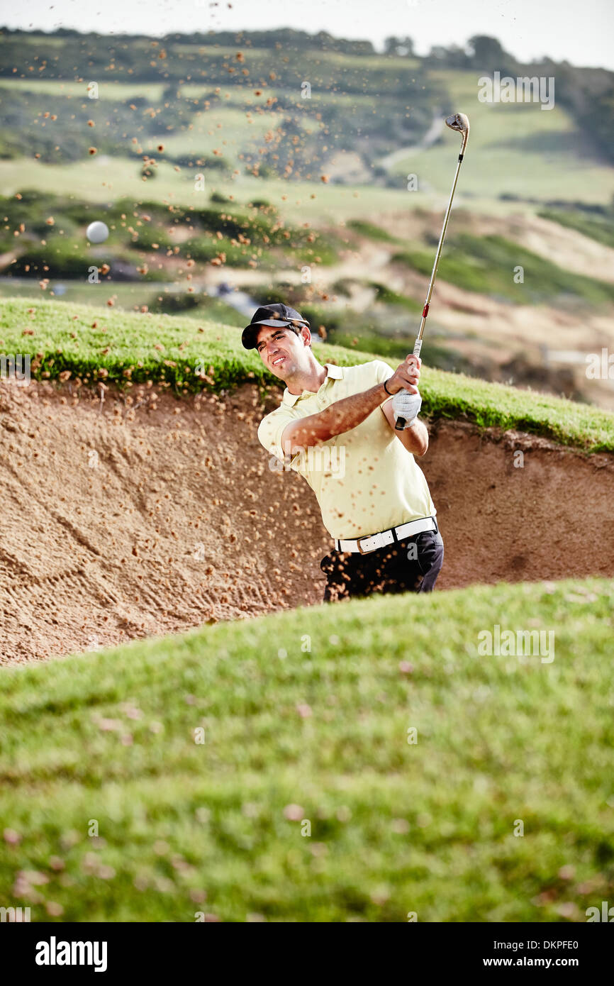 Man swinging from sand trap on golf course - Stock Image