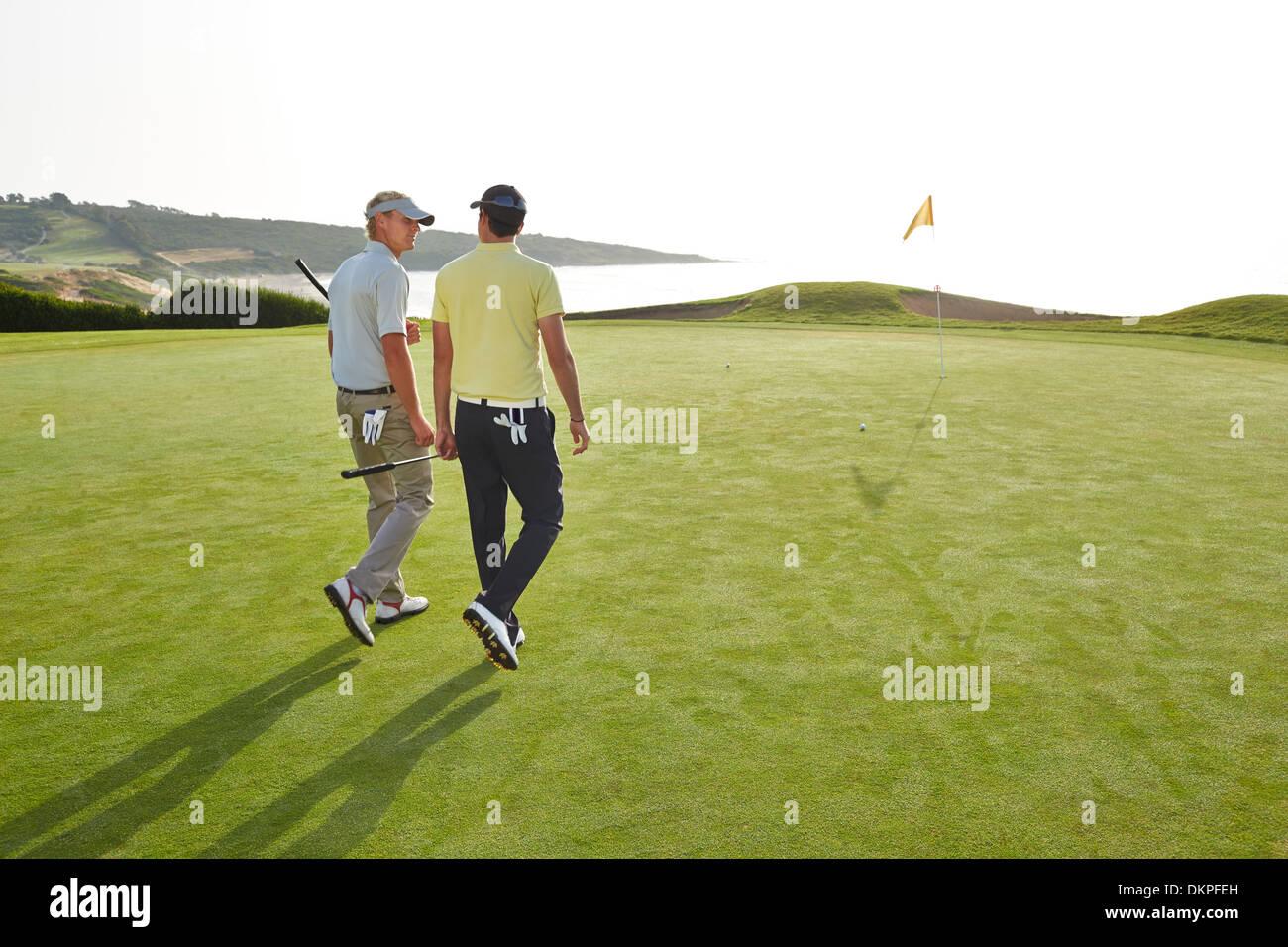 Men walking toward hole on golf course overlooking ocean Stock Photo