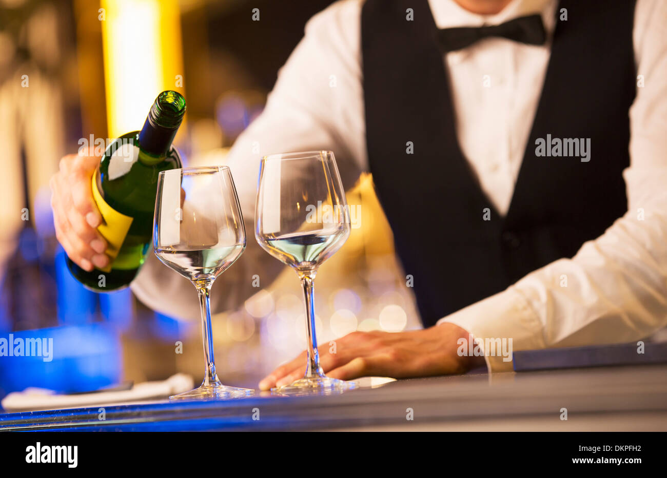 Well dressed bartender pouring wine - Stock Image