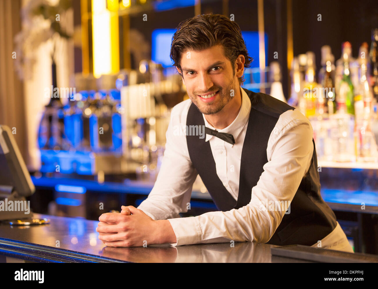 Portrait of well dressed bartender leaning on bar - Stock Image
