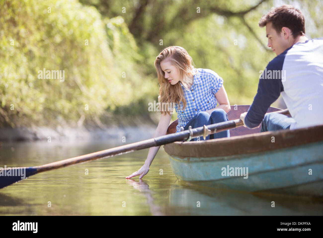 Couple in rowboat on river - Stock Image