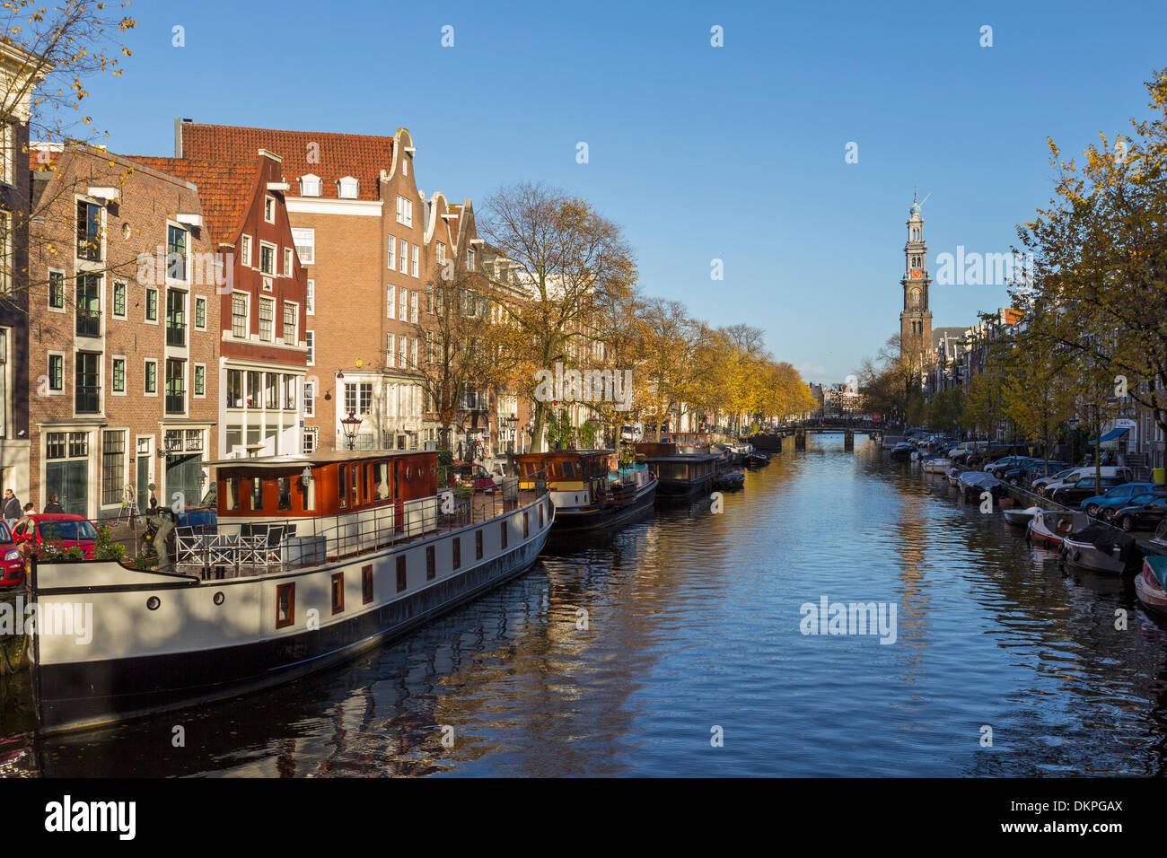 AMSTERDAM  NETHERLANDS THE PRINSENGRACHT CANAL WITH HOUSEBOATS AND THE WESTERKERK TOWER - Stock Image