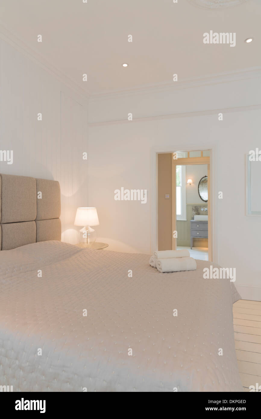 Bed and towels in modern bedroom - Stock Image